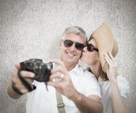 Composite image of vacationing couple taking photo. Vacationing couple taking photo against white background Stock Images