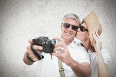 Composite image of vacationing couple taking photo Royalty Free Stock Photos