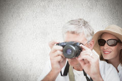 Composite image of vacationing couple taking photo. Vacationing couple taking photo against white background Stock Photos