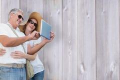 Composite image of vacationing couple taking photo Royalty Free Stock Image