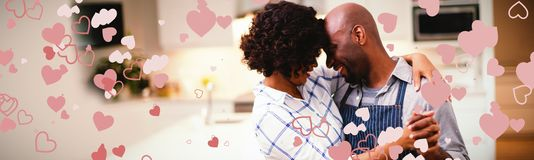 Composite image of valentines heart design. Valentines heart design against romantic couple dancing in kitchen stock images
