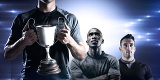 Composite image of victorious rugby player holding trophy Stock Photos