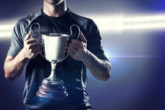 Composite image of victorious rugby player holding trophy Royalty Free Stock Photo