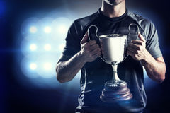 Composite image of victorious rugby player holding trophy Royalty Free Stock Image