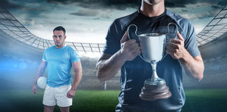 Composite image of victorious rugby player holding trophy Stock Photo
