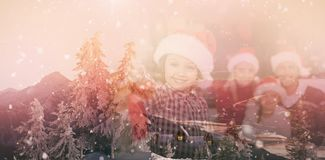 Composite image of view of landscape during snowfall. View of landscape during snowfall against son wearing santa hat holding baubles in front of his family Royalty Free Stock Image