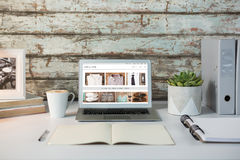 Composite image of vintage shoes. Vintage shoes against overhead view of office desk with laptop and documents Stock Photo