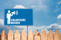 Composite image of volunteers needed. Volunteers needed against fence under blue sky Stock Image