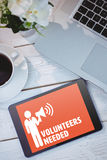 Composite image of volunteers needed. Volunteers needed against tablet and laptop on table Royalty Free Stock Photo