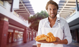 Composite image of waiter holding croissant on a tray Stock Photo
