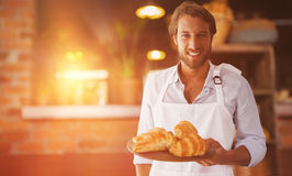 Composite image of waiter holding croissant on a tray Stock Photos