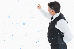 Composite image of waiter pointing something. Waiter pointing something against snow falling Royalty Free Stock Photo