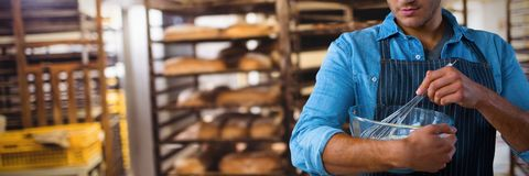Composite image of waiter preparing food. Waiter preparing food against baking trolley in bakery shop royalty free stock photography