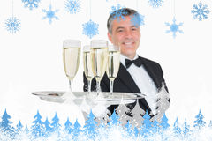 Composite image of waiter serving tray full of glasses with champagne. Waiter serving tray full of glasses with champagne against snowflakes and fir trees Royalty Free Stock Images