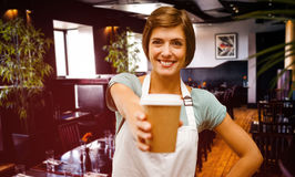 Composite image of waitress pointing away a cup of coffee royalty free stock photos