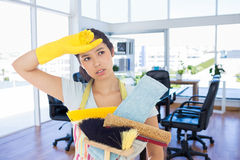 Composite image of weary woman holding cleaning tools. Weary woman holding cleaning tools against board room stock photos