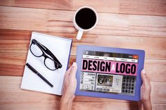 Composite image of webpage for create a logo. Webpage for create a logo against overhead of feminine hands using tablet Royalty Free Stock Images