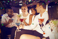 Composite image of well dressed people drinking cocktails in limousine Stock Photos