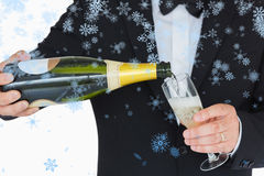 Composite image of welldressed man pouring champagne Stock Photography