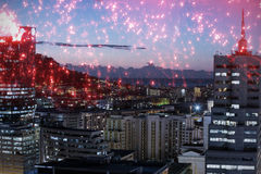 Composite image of white fireworks exploding on black background. White fireworks exploding on black background against illuminated buildings in city against sky Stock Photography
