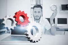 Composite image of white and red cogs and wheels. White and red cogs and wheels against confused computer engineer looking at camera with laptop Royalty Free Stock Image