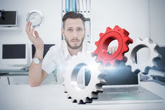 Composite image of white and red cogs and wheels. White and red cogs and wheels against confused computer engineer looking at camera with laptop Royalty Free Stock Photo