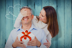 Composite image of wife covering eyes of husband. Wife covering eyes of husband  against wooden planks Royalty Free Stock Photo