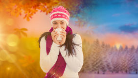 Composite image of winter brunette with coffee Royalty Free Stock Photos