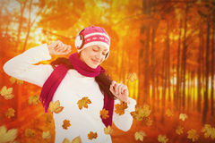 Composite image of winter brunette listening to music Stock Image