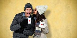 Composite image of winter couple enjoying hot drinks stock photography