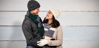 Composite image of winter couple enjoying hot drinks. Winter couple enjoying hot drinks against painted blue wooden planks Royalty Free Stock Image