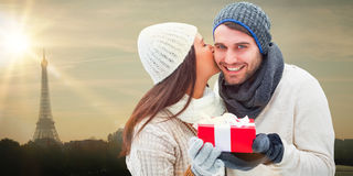 Composite image of winter couple holding gift Royalty Free Stock Photos