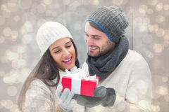 Composite image of winter couple holding gift Royalty Free Stock Photo