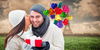 Composite image of winter couple holding gift Royalty Free Stock Image