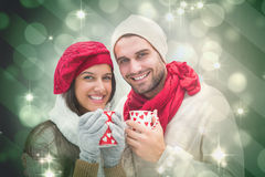 Composite image of winter couple holding mugs Stock Photography
