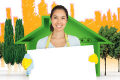 Composite image of woman in apron and rubber gloves holding white surface Royalty Free Stock Images