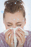 Composite image of woman blowing nose. Woman blowing nose against snow falling Stock Image