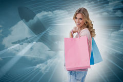 Composite image of a woman carrying shopping bags Royalty Free Stock Photo