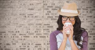 Composite image of Woman with coffee against brick wall Stock Photography