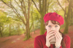 Composite image of woman drinking from a cup. Woman drinking from a cup against peaceful autumn scene in forest stock photo