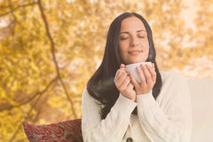 Composite image of woman enjoying a lovely drink. Woman enjoying a lovely drink against tranquil autumn scene in forest stock photo