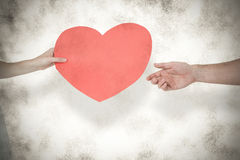 A Composite image of woman giving heart card to her boyfriend Royalty Free Stock Photos