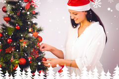 Composite image of woman hanging christmas decorations on tree Stock Photo