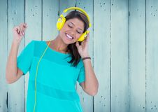 Composite image of Woman with headphones against blue wood panel. Digital composite of Woman with headphones against blue wood panel stock photos