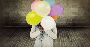 Composite image of woman hiding her face with bunch of colorful balloons Royalty Free Stock Image
