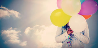 Composite image of woman hiding her face with bunch of colorful balloons Royalty Free Stock Photos