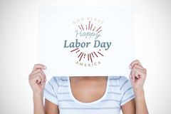 Composite image of woman holding blank sign in front of face. Woman holding blank sign in front of face against digital composite image of happy labor day and Stock Photography