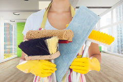 Composite image of woman holding brushes and mops Stock Photo