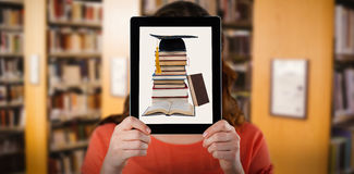 Composite image of woman holding digital tablet in front of her face. Woman holding digital tablet in front of her face against close up of a bookshelf stock photography