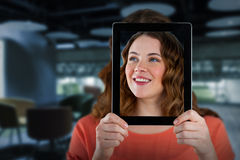 Composite image of woman holding digital tablet in front of her face. Woman holding digital tablet in front of her face against college royalty free stock images